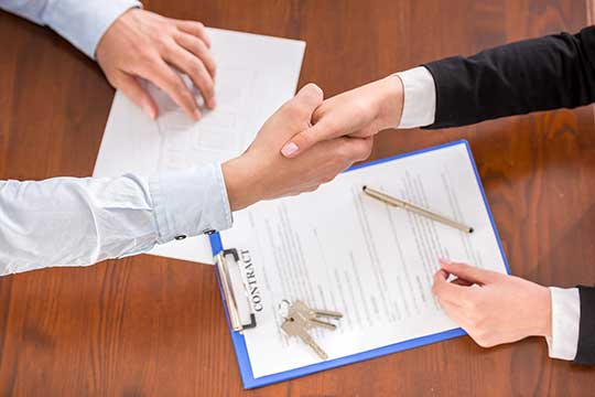 a landlord and tenant shake hands after signing a lease agreement