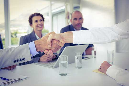 businesspeople shaking hands on a joint venture agreement