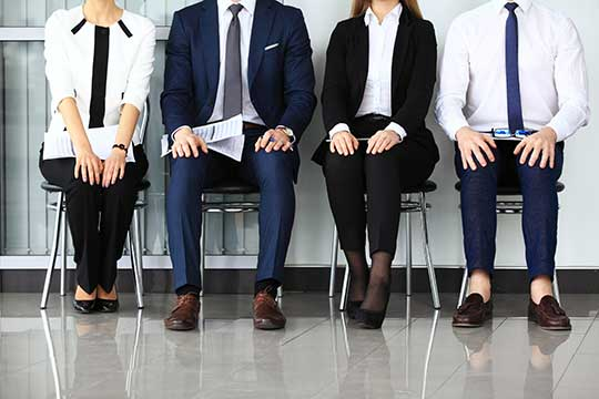 Four employees wait for an interview
