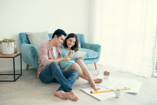 Young couple consult housing plans together in newly purchase home