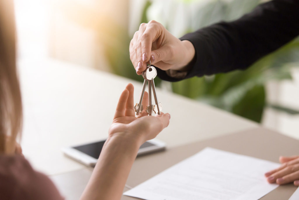 real estate agent handing over keys to new tenant