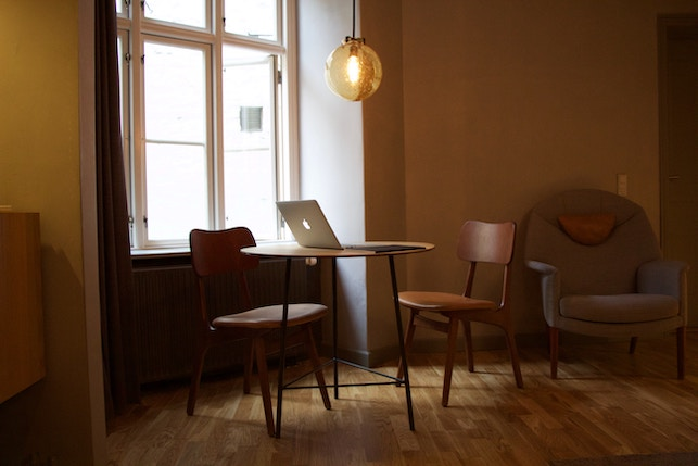 wooden chairs and table with a laptop next to a large window