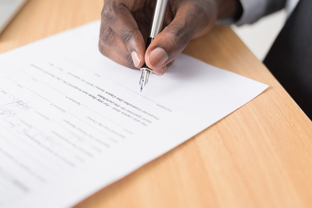 man signing as power of attorney on a document
